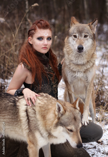 Obraz na plátně Female viking warrior with painted face and with two wolves in winter forest