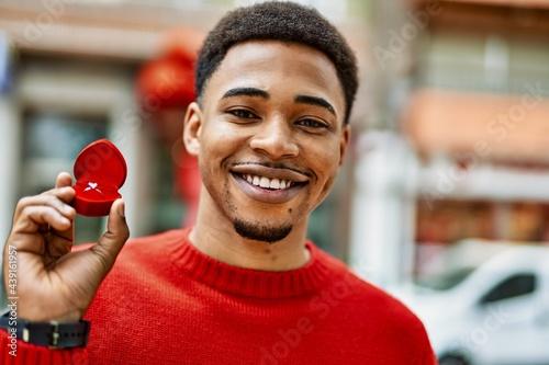 Obraz na plátně Handsome african american young man holding engagement ring