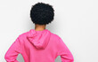Young african american man with afro hair wearing casual pink sweatshirt standing backwards looking away with arms on body