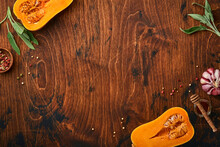 Halves Of Raw Organic Butternut Squash With Sage Leaf, Multicolored Pepper Garlic, Honey, Salt And Pepper On Old Wooden Background. Food Background. Top View With Copy Space.