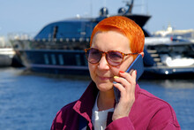 A Conversation On A Mobile Phone. A Beautiful Girl With A Short Haircut Sat On The Pier On The Mooring Bollard. Close-up Of A Sea Yacht In The Background.
