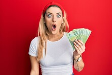 Young Caucasian Woman Holding 1000 Chilean Pesos Scared And Amazed With Open Mouth For Surprise, Disbelief Face