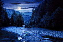 Mountain River Landscape In Summer. Wonderful Nature Scenery At Night. Clouds Rolling Over The Distant Hill In Full Moon Light. Trees Along The Stream In The Valley. Weather With Blue Sky