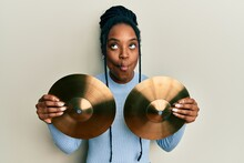 African American Woman With Braided Hair Holding Golden Cymbal Plates Making Fish Face With Mouth And Squinting Eyes, Crazy And Comical.