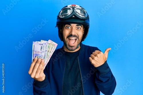 Stampa su Tela Young hispanic man wearing motorcycle helmet holding indian rupee pointing thumb