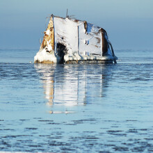 Close-up Of A Fragment Of The Old Sunken Ship In A Frozen Sea. Ice And Snow On The Foreground. Concept Winter Scene. Atmospheric Seascape. Shipwreck, Ecological Issues, Environmental Damage, History