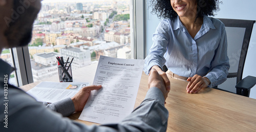 Closeup of Indian latin ceo holding employment contract job offer hiring welcoming female African American newcomer worker manager shaking hands in contemporary office. Human resources concept.