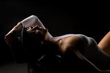 Alluring Woman In Bodysuit In Dark Studio