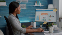 African American Student Typing Financial Investment Analyzing Digital Statistics Using University Online App Webinar. Black Woman Sitting At Desk Working Remote From Home At Commerce Chart On