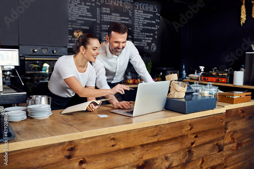 Naklejka premium Two cafe owners working together planning supply orders on laptop