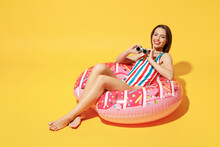 Full Body Length Happy Young Woman Wear Red Blue Swimsuit Sit On Inflatable Ring Look Through Binocular Isolated On Vivid Yellow Color Background Studio Summer Hotel Pool Sea Rest Sun Tan Concept