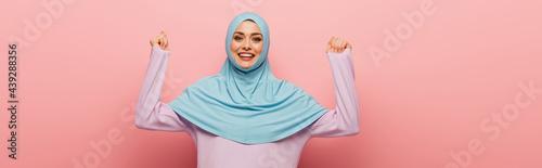 Fotografie, Obraz cheerful muslim woman showing yeah gesture on pink background, banner