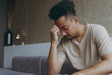 Side View Sad Puzzled Thoughtful Young African American Man Wear Beige T-shirt Sit On Grey Sofa Indoors Apartment Procrastinate Prop Up Forehead Rest On Weekends Stay At Home. Tattoo Translate Fun