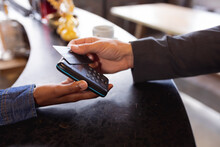 Mid Section Of Man Making A Payment By Credit Card At A Cafe
