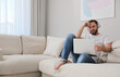 Man with laptop and headphones sitting on sofa at home