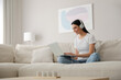 Leinwandbild Motiv Woman with laptop and headphones sitting on sofa at home