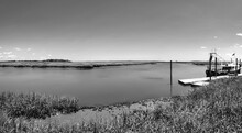 A Panoramic Black And White View Of A Creek, Shrimp Boat And Salt-marsh.