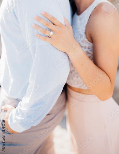 Enamored man and woman embracing, woman hugging man's shoulders, close-up Fototapeta