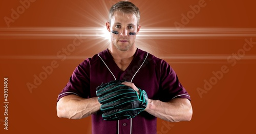 Portrait of caucasian male baseball pitcher wearing gloves against spot of light in background