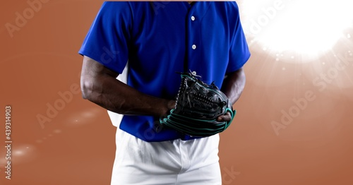 Mid section of african american male baseball pitcher against spot of light on orange background