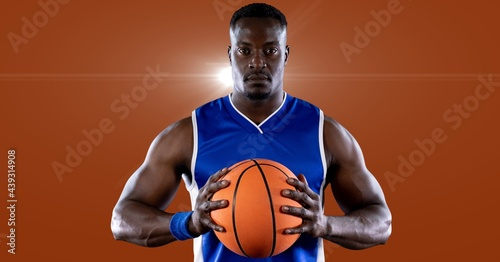 African american male basketball player holding basketball against spot of light in background