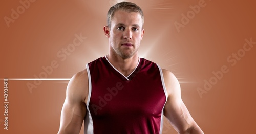 Portrait of caucasian male athlete against spot of light in background