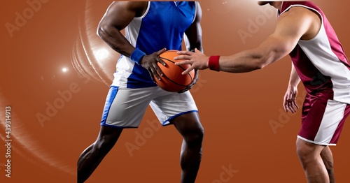 Mid section of two diverse male basketball players playing against spot of light in background