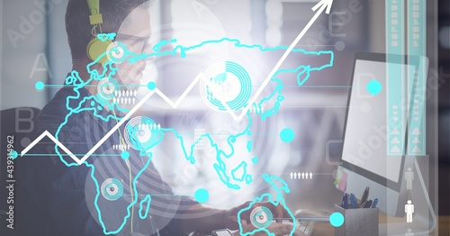 Data processing over world map against caucasian man wearing headphones using computer