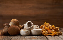 Variety Of Edible Forest Mushrooms On Wooden Board