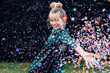 beautiful smiling little girl under a shower of confetti - birthday party carefree celebration concept