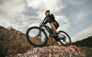 Confident cyclist with e bike in mountains