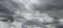 Cumulus Clouds Float Across The Invisible Sky. Large, Wide Clouds Of Various Shapes And Shades Of Gray From Black To White Cover Almost All Of The Blue Sky.