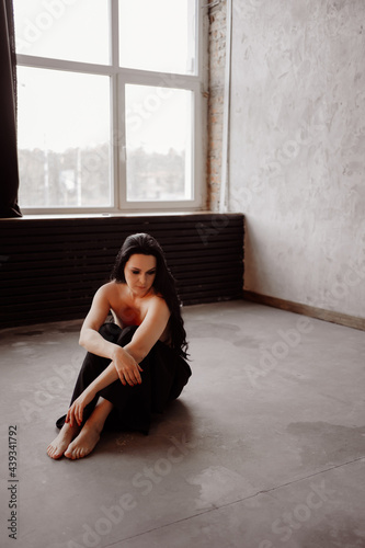 topless. Beautiful and sexy woman with bare breasts and long dark hair on floor.