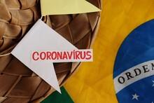 Straw Hat On Top Of Brazilian Flag, With Coronavirus Inscription. Concept Of Feast Of Saint John In Brazil (Festa De São João No Brasil, In Portuguese). Covid-19.