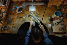 Caucasian Female Jeweller Sitting At Desk, Holding Jewelry Tools, Making Jewelry In Workshop