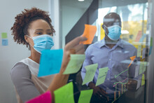Two Diverse Business Colleagues Wearing Face Masks And Taking Notes On Glass Board