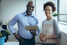 Portrait Of Two Diverse Male And Female Business Colleagues Smiling And Using Tablet