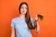 Leinwandbild Motiv Photo of sad brown hairdo young lady look hair wear blue t-shirt isolated on vivid orange color background