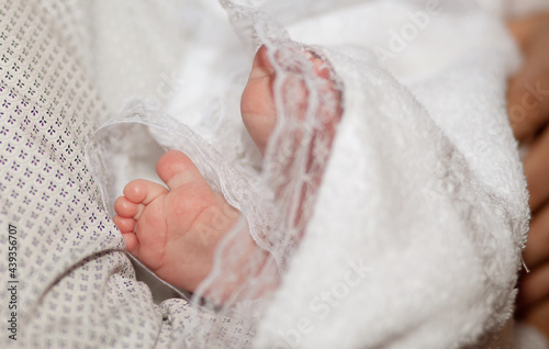 Fotografie, Obraz The sacrament of the baptism of a child in an Orthodox church, the baby's feet in a white veil close-up