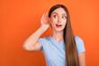 Leinwandbild Motiv Photo of impressed brown hairdo young lady hand ear look empty space wear blue t-shirt isolated on vivid orange color background