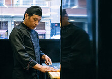 Asian Chef Cutting Salmon With A Knife