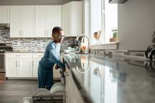 Boy Loads Dishwasher In Bright Kitchen