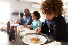 Father And Children Sit At Breakfast Bar Eating Pancakes
