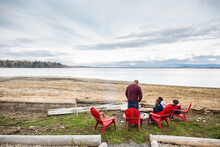 Father And Son Tend Fire Pit In Front Of Beautiful Ocean Landscape
