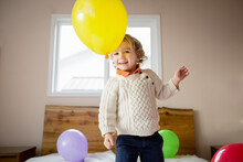 Smiling Boy Stands On Bed Throwing Balloons