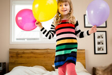 Girl In Rainbow Dress Stands On Bed Holding Balloons