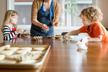 Children Decorate Sugar Cookies At Kitchen Table With Mom