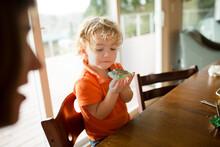 Cute Child Eats Decorated Sugar Cookie At Dining Table