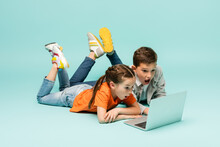 Shocked Children Watching Movie On Laptop While Lying On Blue.