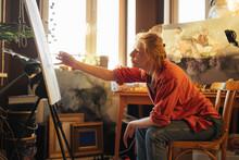 Female Artist Painting In Cozy Workshop